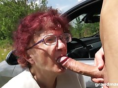 Nerdy mature redhead is so becoming to give a proper blowjob outdoors